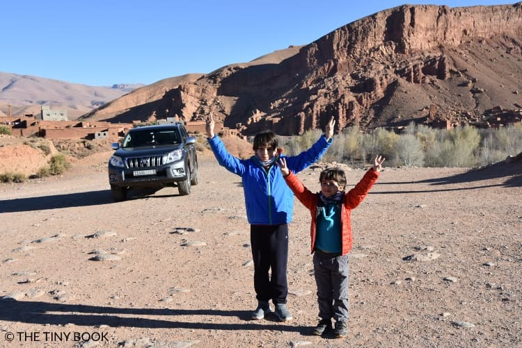 On the road to the desert, car and two kids, Morocco.