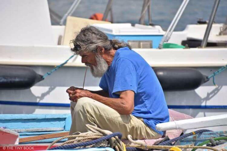 Sailor repairing net in Greece